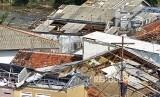 Warga memperbaiki atap rumahnya yang rusak akibat angin puting beliung / Ilustrasi