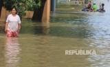 Warga menerobos banjir yang merendam desa Gunungjati, Cirebon, Jawa Barat, Ahad  (11/3).