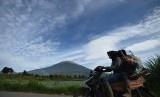 Warga menggunakan sepeda motor dengan latar belakang Gunung Kerinci di Kersik Tuo, Kayu Aro, Kerinci, Jambi, Selasa (30/12).