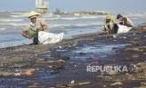 Warga mengumpulkan tumpahan minyak (Oil Spill) yang tercecer di Pesisir Pantai Cemarajaya, Karawang, Jawa Barat, Senin (22/7/2019).