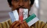 Warga menunjukan Kartu Indonesia Sehat (KIS), Kartu Keluarga Sejahtera (KKS) dan Kartu Indonesia Pintar (KIP) saat pembagian tiga jenis kartu sakti itu di Kampung Melayu, Jakarta Timur, Rabu (13/5). (Republika/Agung Supriyanto)