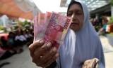 Warga menunjukkan uang zakat konsumtif yang diterimanya dari lembaga penyaluran zakat Baitul Mal  (ilustrasi)