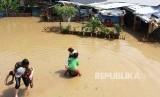Warga menyelamatkan anggota keluarganya saat rumah mereka terendam banjir akibat luapan sungai Cisadane di kawasan Karawaci, Tangerang, Banten, Jumat (26/4/2019).