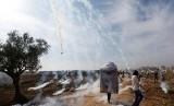 Warga Palestina berhamburan setelah ditembak gas air mata oleh tentara Israel