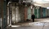 Warga Palestina berjalan melintasi pertokokoan yang tutup sebagai aksi  mogok massal di Kota Hebron, Tepi Barat, Palestina.