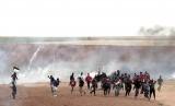 Warga Palestina berlarian saat tentara Israel menembak dengan gas air mata di Jalur Gaza, Selasa (3/4).