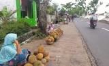 Warga terdampak gempa berjualan durian di depan lokasi pengungsian di Desa Kekait, Kecamatan Gunungsari, Lombok Barat, NTB, Jumat (9/11).