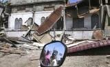 Warga terlihat dalam cermin sepeda motor saat mereka menyaksikan bangunan yang rusak setelah gempa di Pidie Jaya, Provinsi Aceh, Indonesia, Rabu, (7/12).