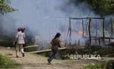 Wartawan berjalan di dekat rumah-rumah yang terbakar di desa Gawdu Thara di kota Maungdaw, Negara Bagian Rakhine, Myanmar barat. Militer Myanmar disebut tak melaporkan kasus pembantaian Rohingya secara utuh. Ilustrasi.