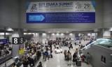 Wisatawan beraktivitas di bawah spanduk pengumuman pengalihan arus saat Pertemuan G20 mendatang, di Bandara Internasional Kansai, Osaka, Jepang, Senin (24/6/2019).