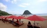 Wisatawan menikmati suasana pantai dengan latar belakang Pulau Merah di Banyuwangi, Jawa Timur, Jumat (7/12/2018). Pulau Merah yang tercipta dari magma gunung api purba itu, telah ditetapkan sebagai situs Geopark Nasional.