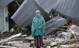 Yuslifa berpose di depan rumahnya yang rusak akibat likuifkasi di Lere, Palu, Sulawesi Tengah.